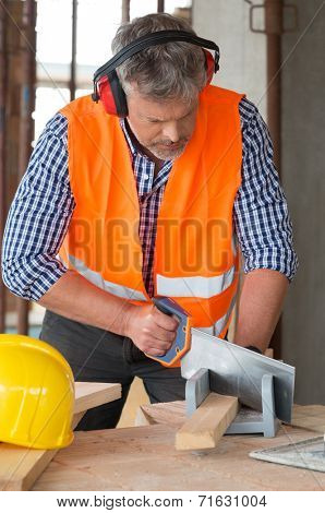 Portrait Of A Male Carpenter Cutting Wood Wearing Earmuffs On Site