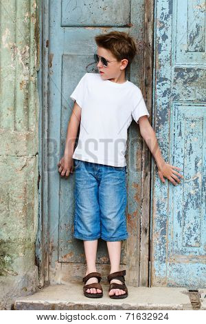 Outdoors portrait of cute boy in a city against old door background