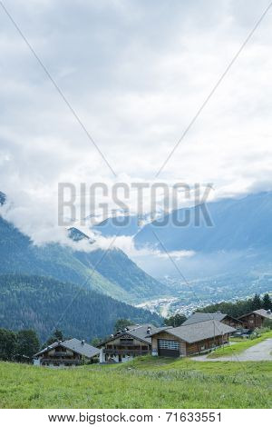 COL DE VOZA, FRANCE - AUGUST 24: Chalets with Les Houches village in the background. Les Houches is one of the Tour du Mont Blanc villages. August 24, 2014 in Col de Voza.