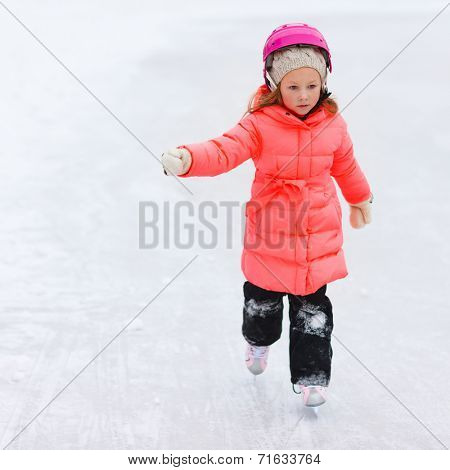 Adorable little girl outdoors on beautiful winter day ice skating