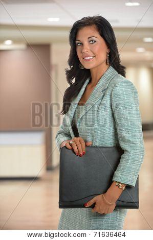 Businesswoman holding binder inside office building