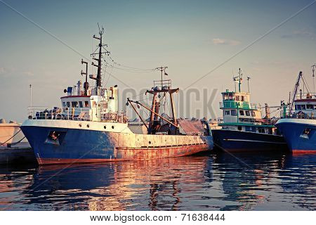 Industrial Fishing Boats Are Moored In Port. Vintage Toned Photo