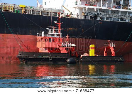 Red Support Tug And Big Cargo Ship. Burgas Port, Bulgaria