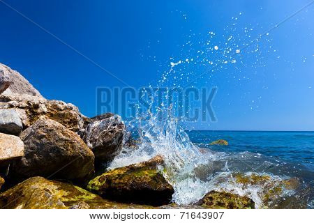 Waves hitting rocks on a tropical beach forming a splash shape. Greece, Santorini.