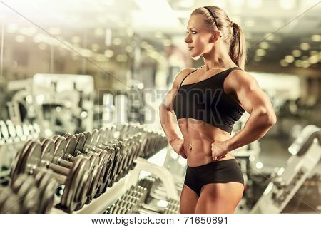 Young woman bodybuilder in gym.