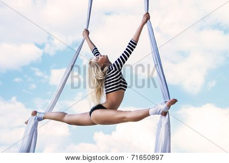 Young woman gymnast. On sky background.