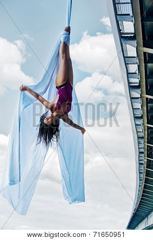 Young woman gymnast. On city and sky background.