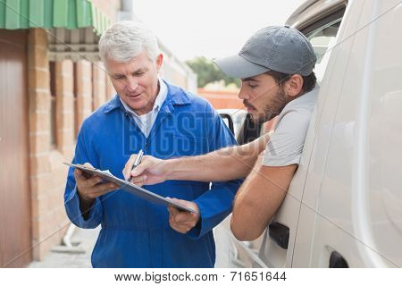 Delivery driver showing customer where to sign outside the warehouse
