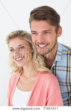 Close up of attractive young couple looking away over white background