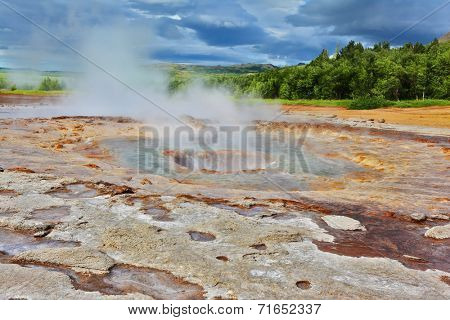Fumaroles Geyser Strokkur. Water vapor from the crater geyser under bizarre clouds. Summer Iceland