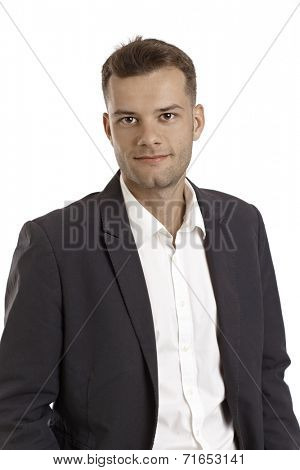 Young businessman smiling in jacket and shirt.