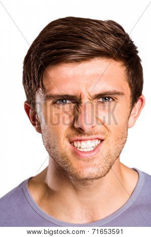 Angry young man growling at camera on white background