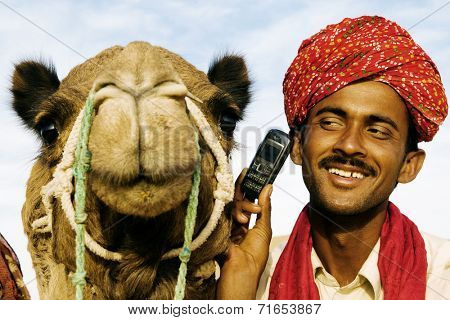 Asian man and camel in the desert with communication, Rajasthan, India.