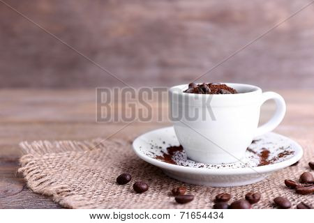 Mug of coffee beans and ground coffee on sackcloth on wooden table on wooden  background