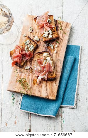 Bruschettas With Blue Cheese And Ham On Grilled Crusty Bread On Blue Wooden Background