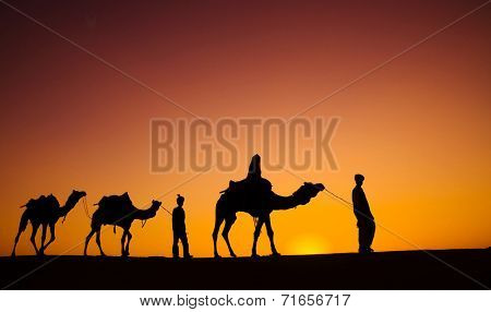 Indigenous Indian men walking through the desert with their camel.