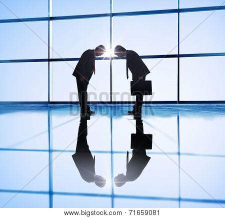 Two businessmen Bowing in Back Lit