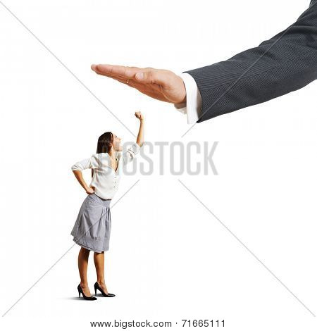 concept photo of conflict between subordinate and boss. discontented businesswoman looking up at big palm of his boss and showing fist. isolated on white background