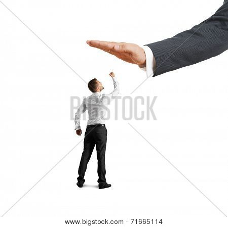 concept photo of conflict between subordinate and boss. screaming young businessman showing fist and looking up at big palm of his boss. isolated on white background