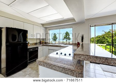 White Kitchen Room With Black Appliances And Granite Tops