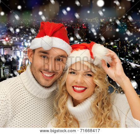 winter, holidays, christmas and people concept - smiiling couple in sweaters and santa helper hats over snowy night city background