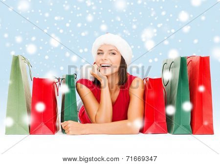 sale, gifts, christmas, x-mas concept - smiling woman in red shirt and santa helper hat with shopping bags