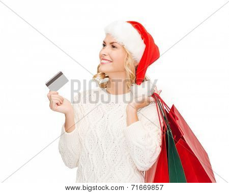sale, gifts, christmas, x-mas concept - smiling woman in santa helper hat with shopping bags and credit card