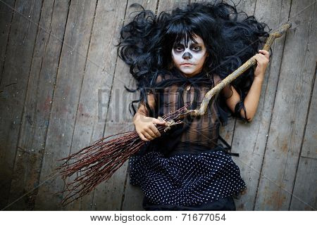 Portrait of cute Halloween girl with broom looking at camera