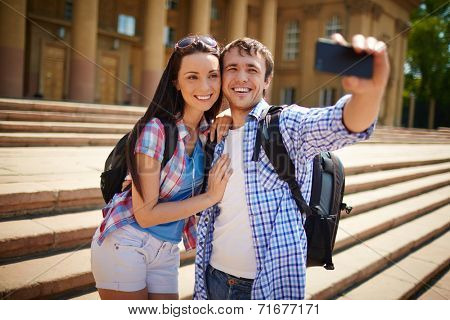 Couple of young travelers taking photo of themselves in ancient town
