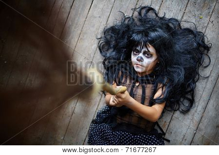 Portrait of eerie girl with broom looking at camera with sulky expression