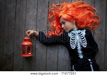 Portrait of cute girl in red wig and Halloween costume