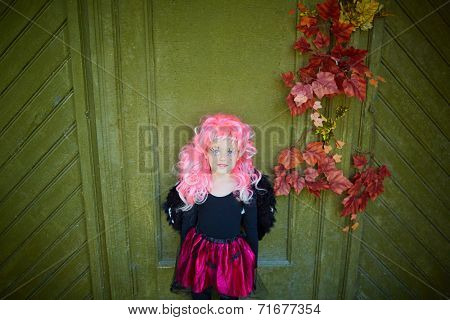 Portrait of cute girl wearing Halloween attire and pink wig looking at camera