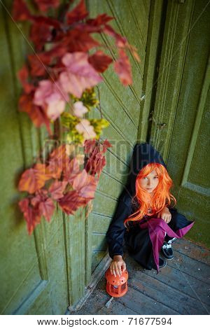 Halloween girl in traditional costume sitting on the porch of dilapidated house