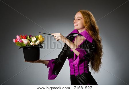 Female magician doing tricks on grey background