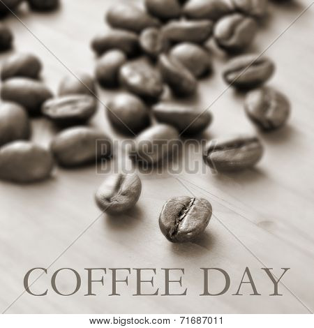 the text coffee day and a pile of roasted coffee beans on a wooden table, in duotone