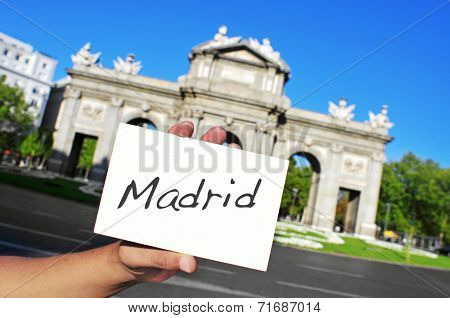 a man holding a signboard with the word Madrid written in it in front of La Puerta de Alcala in Madrid, Spain