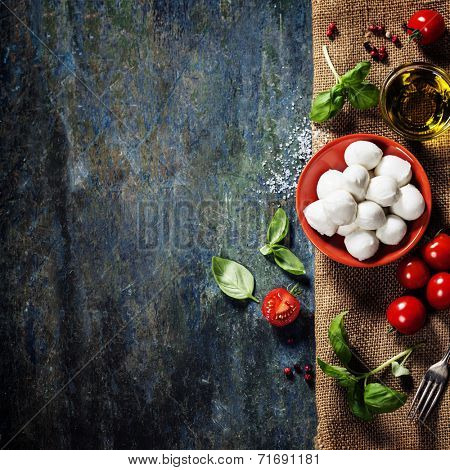 Cherry tomatoes, basil leaves, mozzarella cheese and olive oil for caprese salad. Lots of copy space