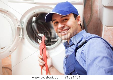 Smiling technician repairing a washing machine