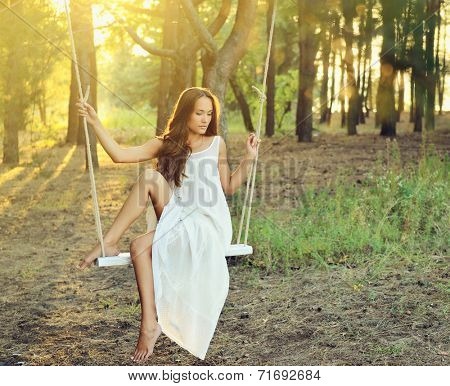 Young woman is swinging on a swing in summer pine forest. Image toned and noise added.