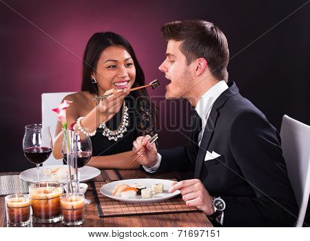 Woman Feeding Man In Restaurant