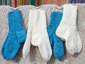 foto of thread-making  - wool white and blue socks hanging on simple cloth - JPG
