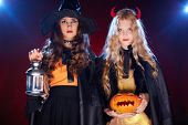 picture of antichrist  - Two girls with lantern and pumpkin looking at camera - JPG