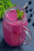 image of masonic  - Blueberry smoothie in a mason jar with a straw and sprig of mint