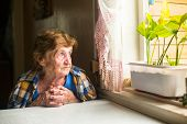 stock photo of lonely woman  - Lonely old woman sitting by the window in his cottage - JPG