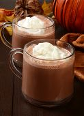 stock photo of whipping  - Two cups of hot chocolate with whipped cream on a holiday table - JPG