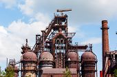stock photo of blast-furnace  - building a blast furnace at the steel industry on a background of blue sky - JPG