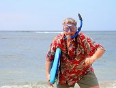 Tourist with snorkel gear and surfboard on a tropical beach poster