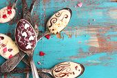 pic of chocolate spoon  - Spoons with tasty chocolate for party on old blue wooden table - JPG