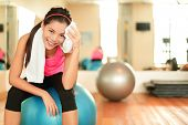 stock photo of health center  - Fitness woman in gym resting on pilates ball - JPG