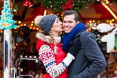 pic of merry-go-round  - Man and woman or  a couple  or friends during advent season or holiday in front of a carousel or  - JPG